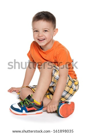 A portrait of a laughing preschool boy on the white background - stock photo
