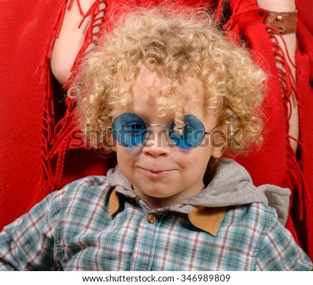 a portrait of a little blond curly boy with blue eyeglasses - stock photo