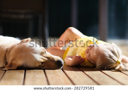 A portrait of a little cute toddler girl relaxing with her dog, a yellow labrador on the wooden deck in the sun