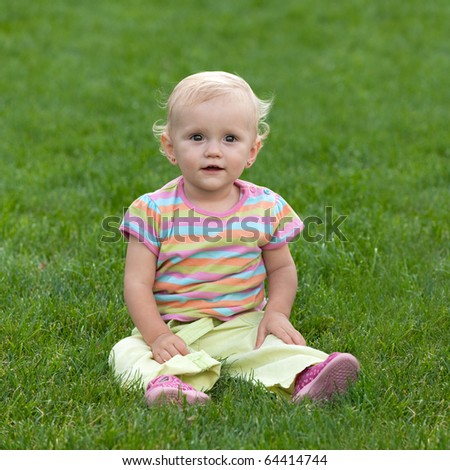 A portrait of a little girl on the grass