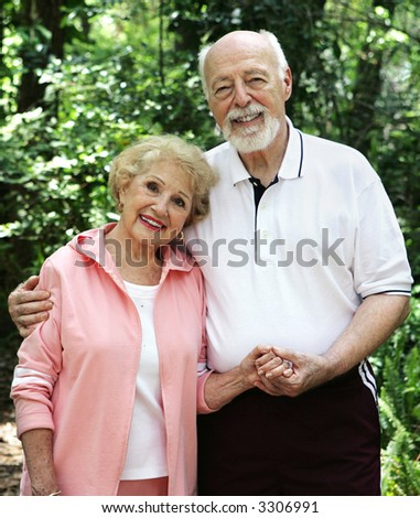 A portrait of a loving senior couple holding hands outdoors. - stock photo