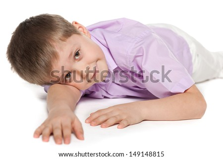 A portrait of a lying young boy on the white background