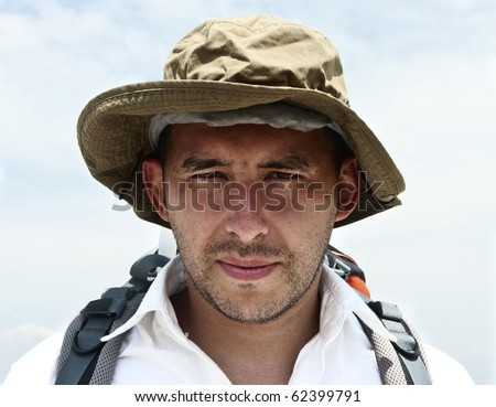 A portrait of a masculine white man in his mid 30ies with a backpack - stock photo