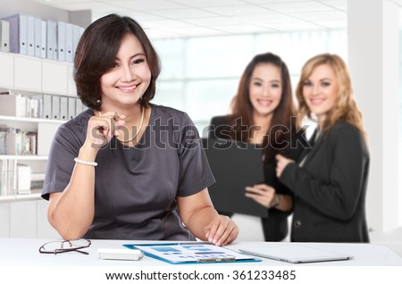A portrait of a Mature businesswoman with young businesswoman on the background - stock photo