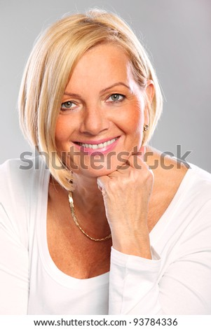 A portrait of a mature elegant woman smiling over grey background - stock photo