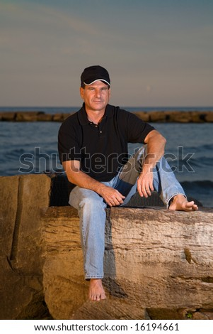 A portrait of a mature man - age 56 - sits on rocks by Lake Erie in Cleveland Ohio watching a sunset. - stock photo