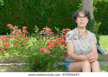 a portrait of a mature woman sitting in garden