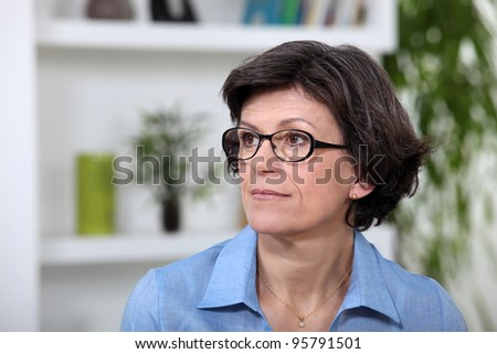 A portrait of a middle age woman in her living room. - stock photo