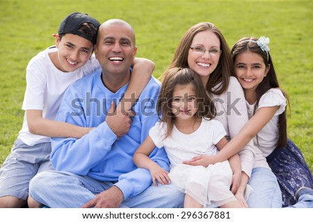 A portrait of a mixed ethnicity family, mum and dad have three cute children between the ages of 4 to 10. They are sitting down and smiling happily at the camera. - stock photo