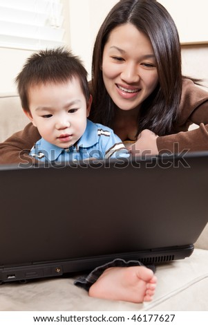 A portrait of a mother and a son using a laptop - stock photo