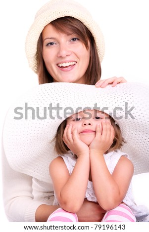 A portrait of a mother and her baby girl, both in hats over white background - stock photo