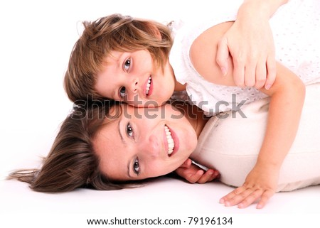 A portrait of a mother and her baby girl lying on the floor and hugging over white background - stock photo