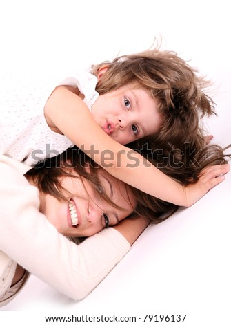 A portrait of a mother and her baby girl lying on the floor and playing over white background - stock photo