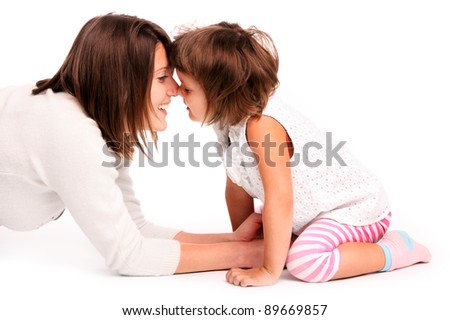 A portrait of a mother and her baby girl touching noses over white background - stock photo