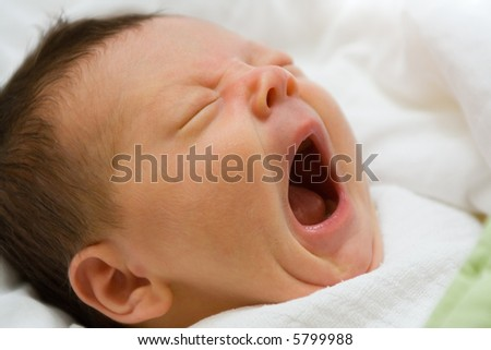 A portrait of a newborn infant girl with her mouth wide open in a big yawn. - stock photo