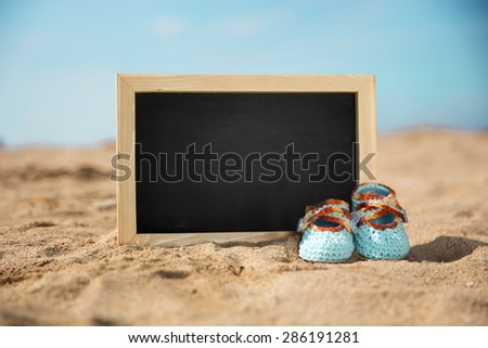 A portrait of a pair of blue knit toddler shoes and mini chalkboard, sand on the beach background - stock photo