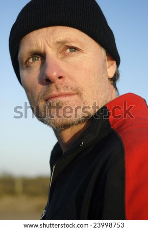 A portrait of a pensive looking man wearing a black knitted hat. - stock photo