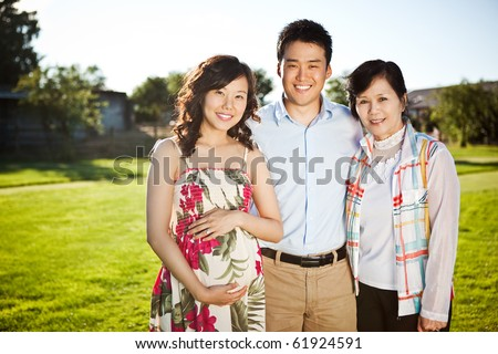 A portrait of a pregnant asian woman with her husband and her mother outdoor