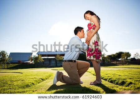 A portrait of a pregnant wife with her husband kissing her belly - stock photo