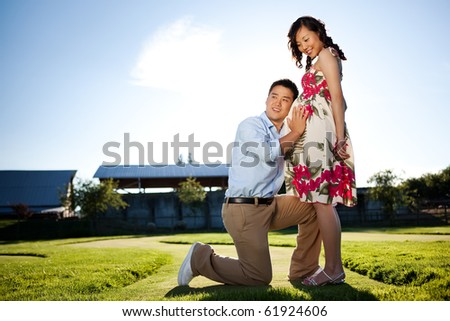 A portrait of a pregnant wife with her husband listening to her belly - stock photo