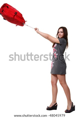 A portrait of a pretty girl pulling a big red bag - stock photo