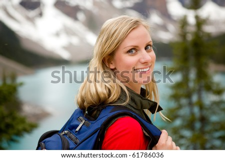 A portrait of a pretty woman in front of a mountain landscape, Lake Moraine, Alberta, Canada - stock photo