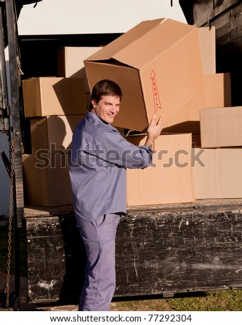A portrait of a professional mover carrying cardboard boxes