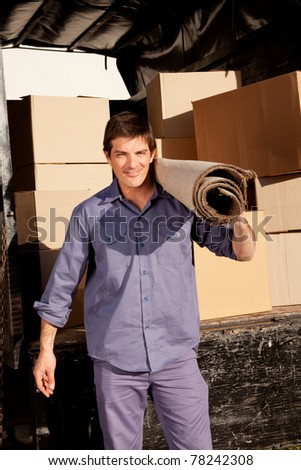 A portrait of a professional mover with a carpet and boxes in the background - stock photo
