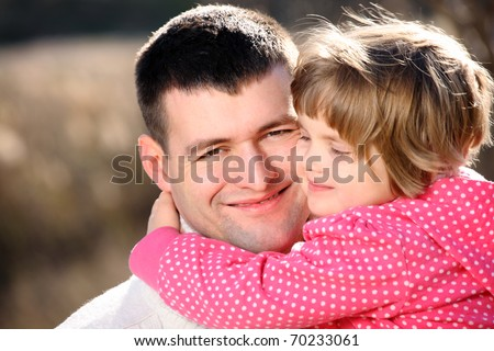 A portrait of a proud father with his baby girl hugging in the park - stock photo