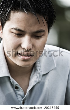 A portrait of a sad young asian male - stock photo