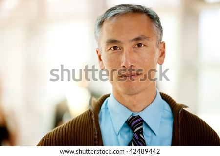 A portrait of a semi casual business man with colleagues in the background - stock photo