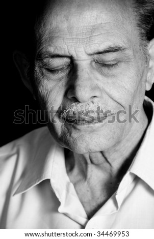 A portrait of a senior Asian man with his eyes closed. Monochrome. - stock photo
