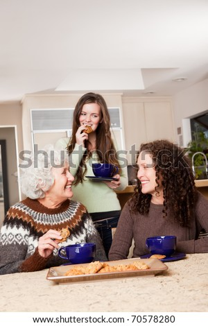 A portrait of a senior lady at home with her daughter and granddaughter - stock photo