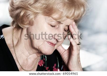 A portrait of a senior lady having headache over dark background - stock photo