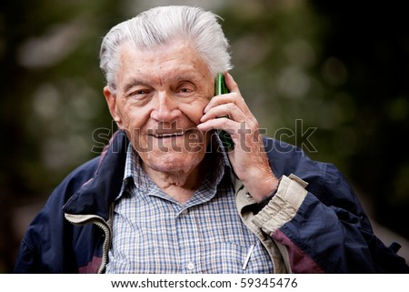 A portrait of a senior using a cell phone outdoors - stock photo