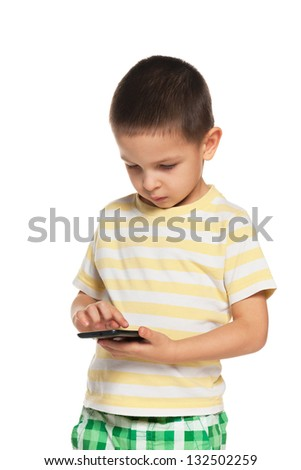 A portrait of a serious little boy with a smartphone - stock photo