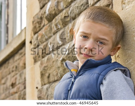 A portrait of a serious looking young boy leaning against a wall - stock photo