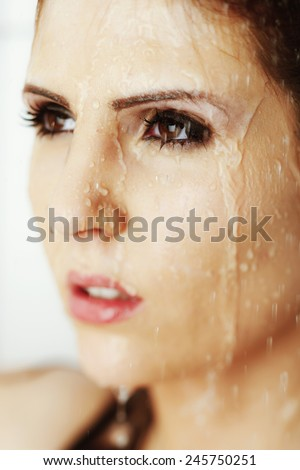 A portrait of a sexy young model with perfect skin and standing in the shower.