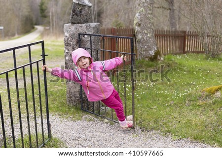 a portrait of a small cute girl wearing pink clothing playing with the fence and the gate outdoors