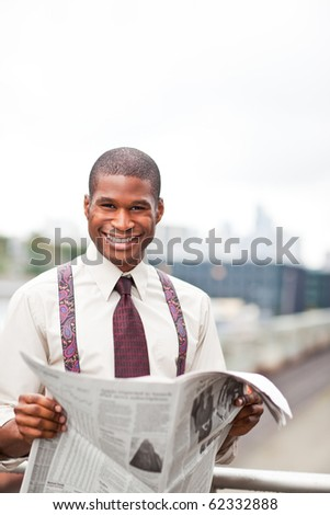 A portrait of a smiling black businessman reading newspaper outdoor - stock photo