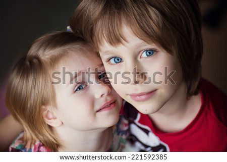 A portrait of a smiling cute little boy and girl embracing each other close up. Funny kids. Happy family.  - stock photo