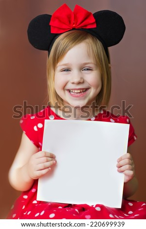 A portrait of a smiling cute little girl with empty blank in hands, isolated on brown, close up. Holidays concept. Invitation. Funny kids. Masked ball. Halloween. - stock photo