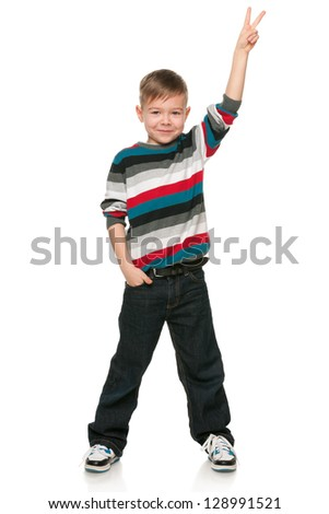 A portrait of a smiling little boy shows victory sign on the white background