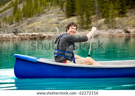 A portrait of a smiling man in a canoe on a glacial lake - stock photo