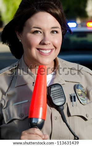 a portrait of a smiling police officer as she holds an orange flashlight traffic control cone.