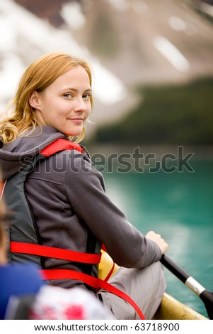 A portrait of a smiling woman in a canoe on a glacial lake.