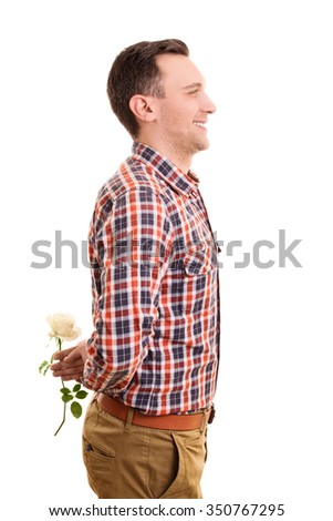 A portrait of a smiling young man hiding a flower isolated on white background. - stock photo