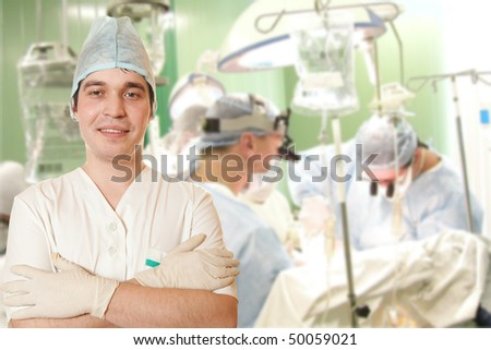 A portrait of a surgeon while an operation is being conducted in the background - stock photo
