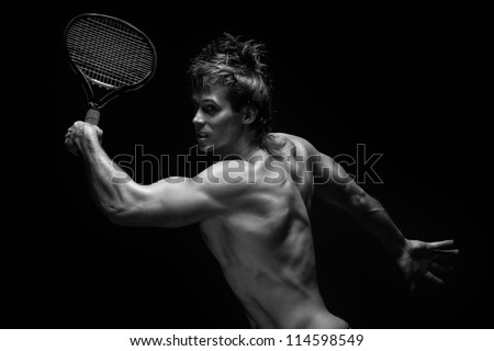 A portrait of a tanned sportive tennis player with a racket against black background. - stock photo