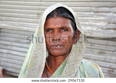 A portrait of a very poor woman from India who makes a living either in making small objects for sale or begging.
